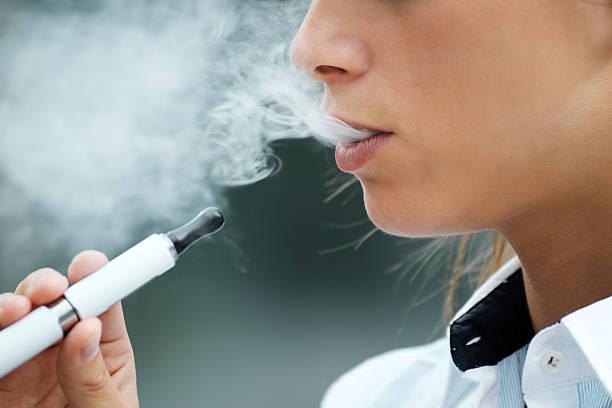 closeup of woman smoking e-cigarette and enjoying smoke. Copy space